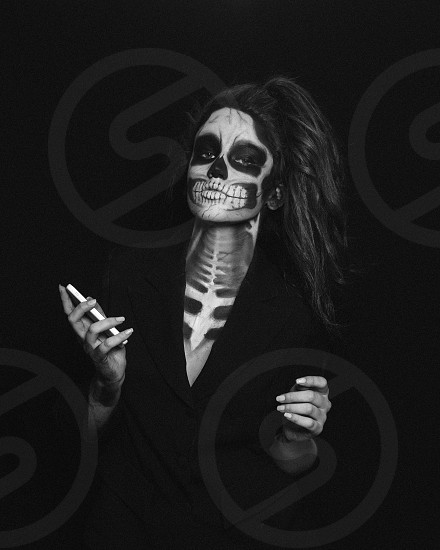 woman in black button up shirt with skull face paint photo