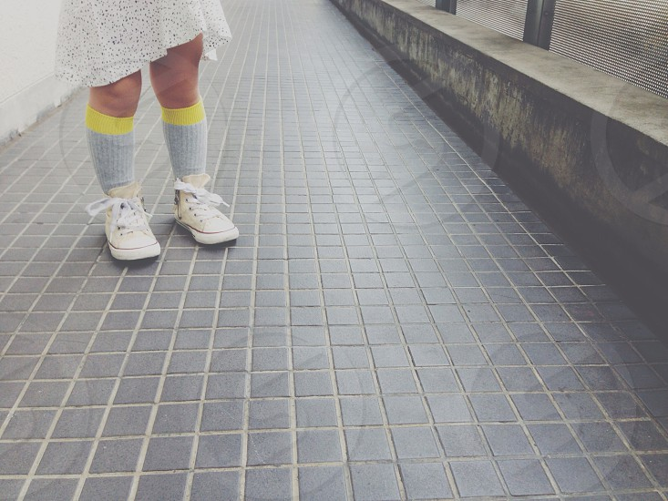 girl wearing grey and yellow knee socks and white converse all star high tops standing photo