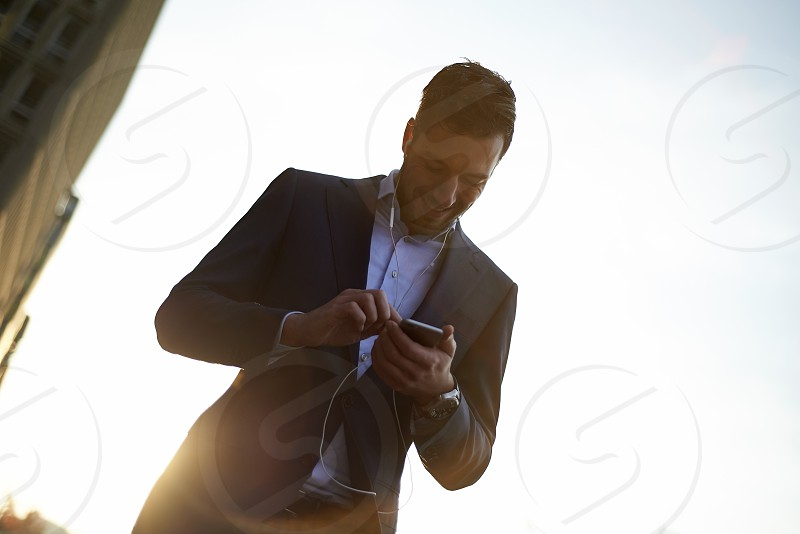 A young business man outside in an urban area of the city walking using his mobile phone for mobile payment in early morning sunrise photo