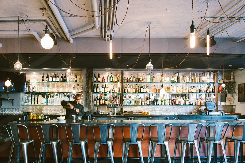 man in black shirt pouring a liquor on glass in front of brown bar counter with grey metal bar stool photo