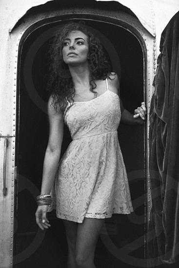 woman in white lace spaghetti strap sundress standing in the doorway of an airstream trailer photo