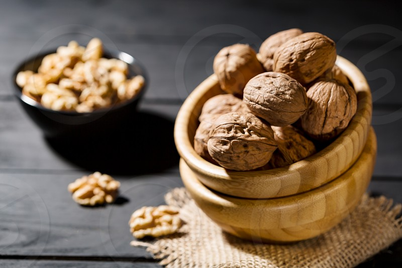 Superfood concept. Whole walnut in wood bowl on dark background with copy space. photo
