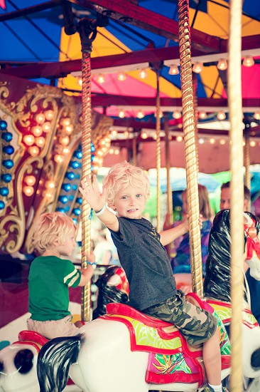 carousel fair carnival merry-go-round horses amusement park ride boy boys children child fun happy youth play sit wave family hold circles snacks treats summer midway photo