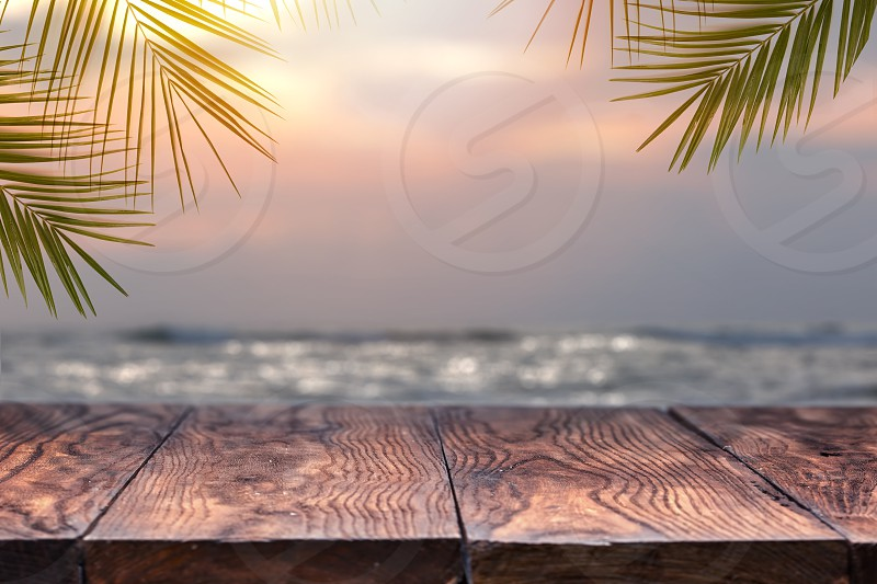 Top of wood table on blurred sea on the sunset with coconut tree background . Empty ready for your product display montage. Concept of beach in summer. photo