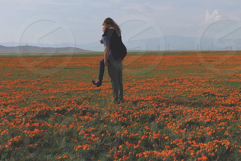 man carrying a woman on his back through a field of orange flowers photo