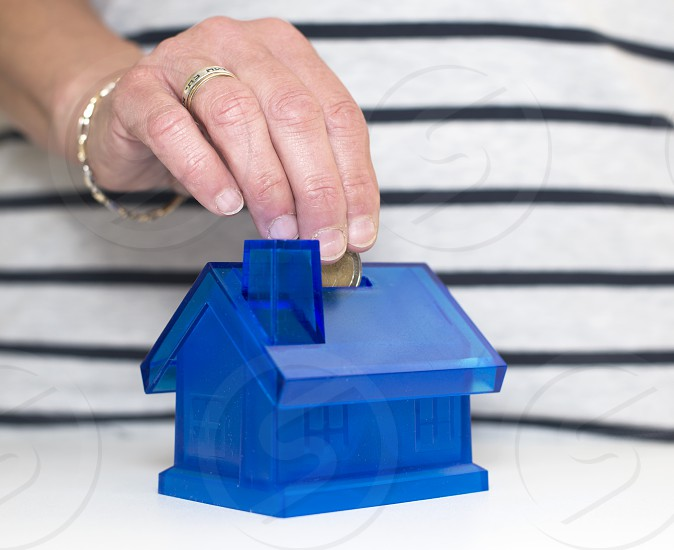 female hand putting money in the house photo
