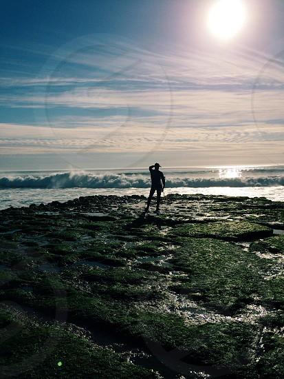 man standing gray stone near seashore facing sunlight photo