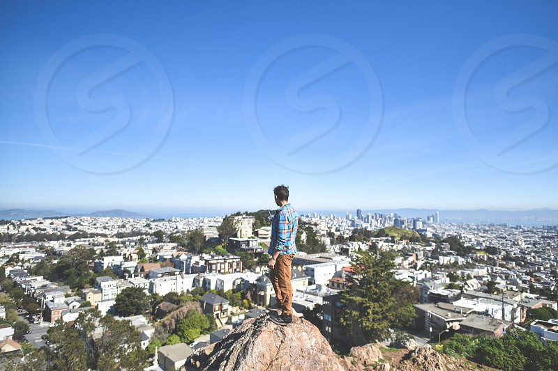 man guy centered city view san francisco rock looking scope sky photo