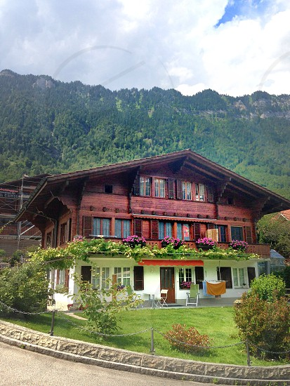 Typical and traditional large wood panel A-frame house in Switzerland with flower boxes. In front of Swiss Alps.  photo