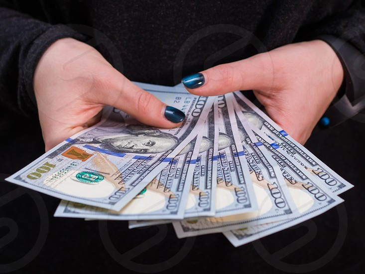 Woman hand with dollars isolated on black background. Girl counting money. photo