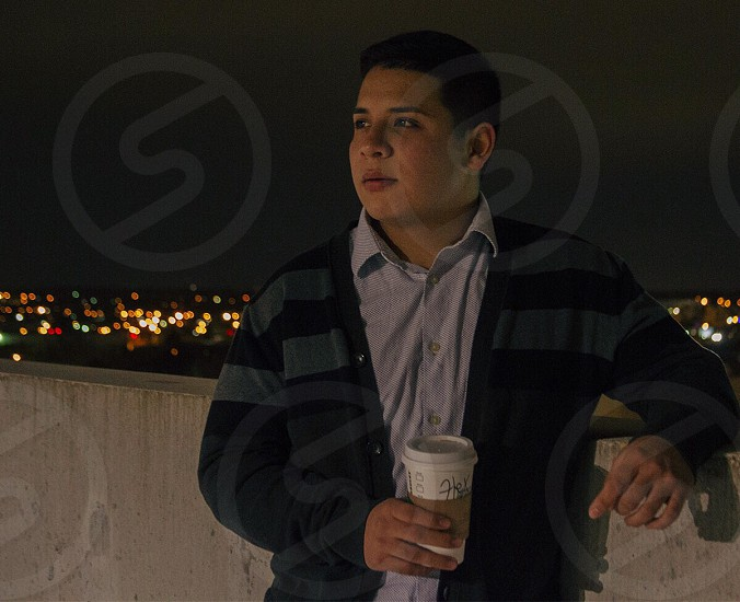 man wearing black and gray stripe jacket holding white disposable cup photo