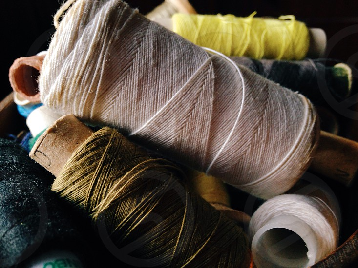 pile of brown white black yellow and blue nylon thread rolls photo