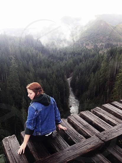 woman sitting on the wooden bridge photo