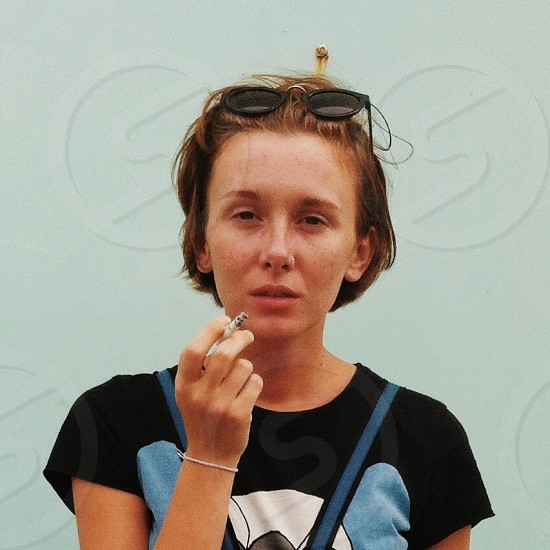 woman in black t shirt with print holding cigarette stick photo