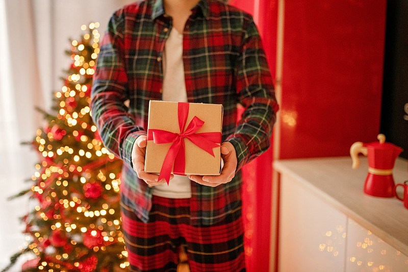 Adult man holds in his hand a box with a gift for Advent holiday. Happy New Year and Merry Christmas photo