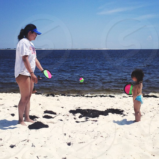 woman and daughter playing near seashore photo