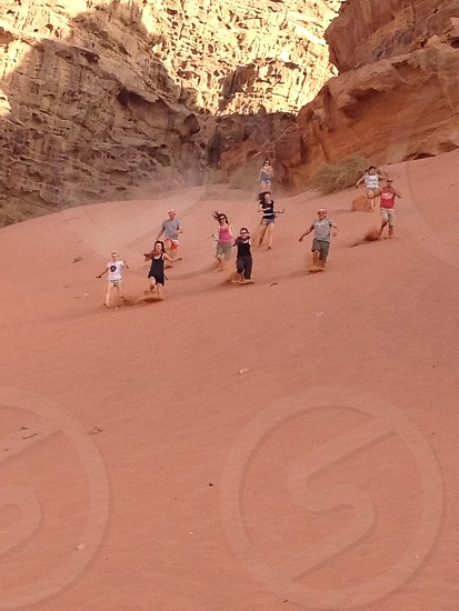 group of people running down on desert sands with rock mountain behind photo