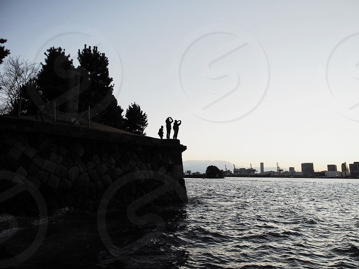 silhouette of three figures standing on seawall taking photos of large body of water and cityscape photo