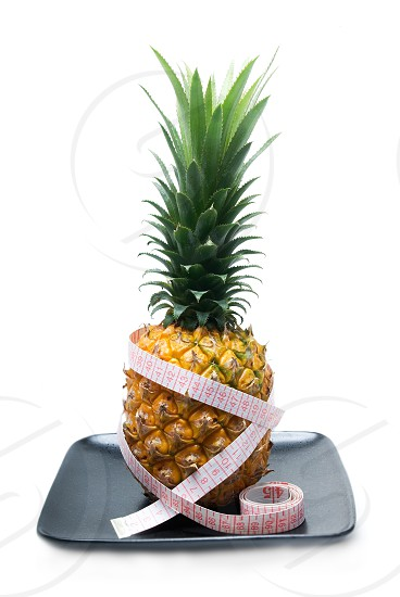 pineapple on a black plate with tape meter isolated on white background photo