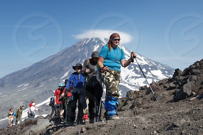AVACHA VOLCANO KAMCHATKA PENINSULA RUSSIAN FAR EAST - JULY 08 2014: Hiking on the Kamchatka Peninsula - a group of tourists go hiking and climbing to the top of Avacha Volcano on background of Koryak Volcano. photo