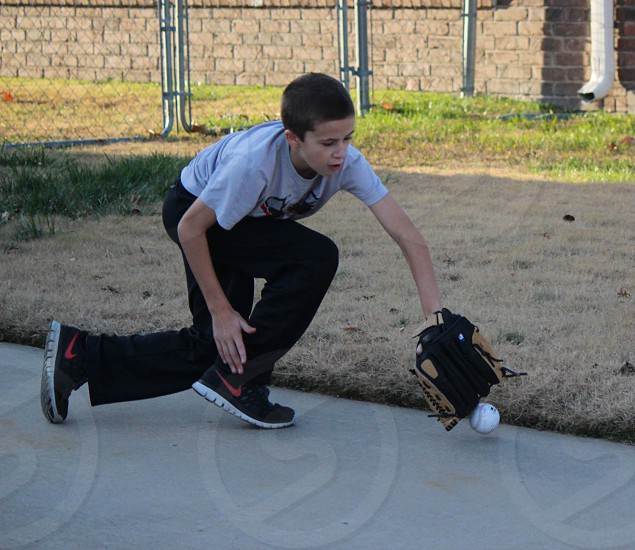 Young boy dives to catch baseball. photo