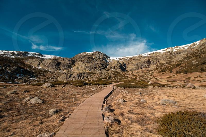Wooden walk towards the mountain. photo
