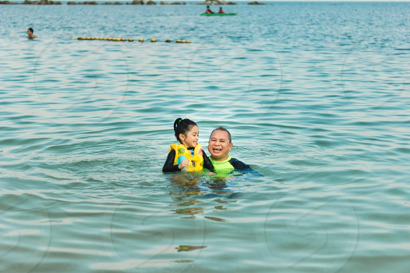 father and child wearing green floater vest on body of water photo