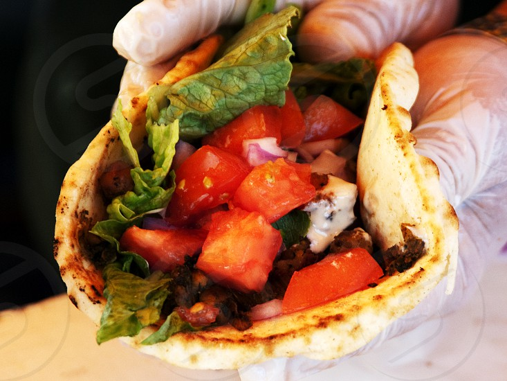 Fair or festival pita stuffed with veggies mushrooms and taziki sauce in gloved hands photo