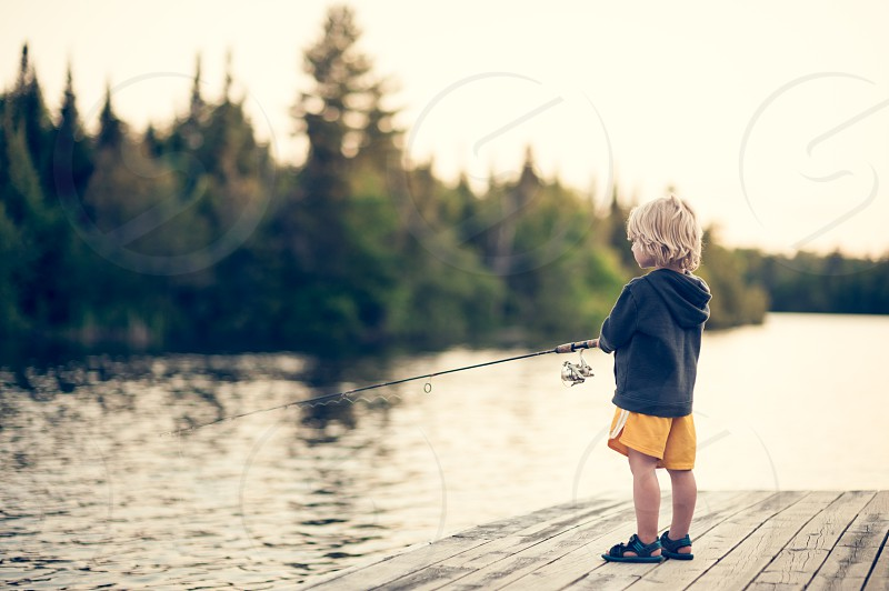 child fishing boy youth kid sweatshirt lake water dock blue navy yellow trees fish pole rod blonde hair sandals reel sunset dusk evening forest woods vacation relax peaceful serenity wilderness outdoors outside alone solo photo