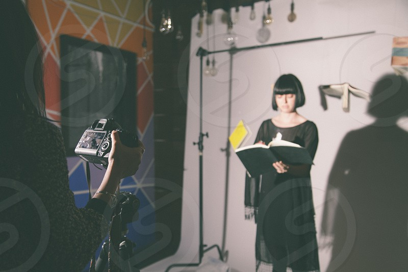 woman in black boat neck long sleeve dress holding and flipping the pages of black book while standing in front of the camera held by person inside the studio photo
