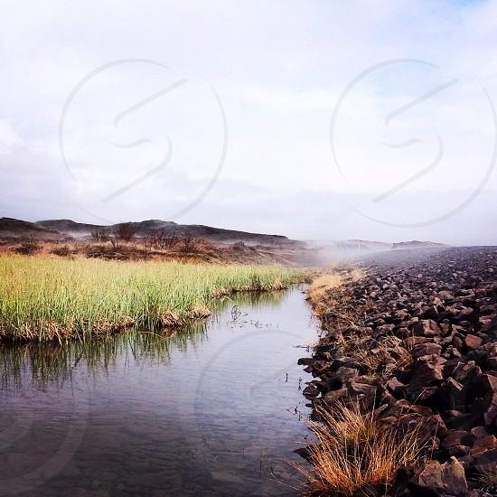 Grass steam water rocks bush mountains..  photo