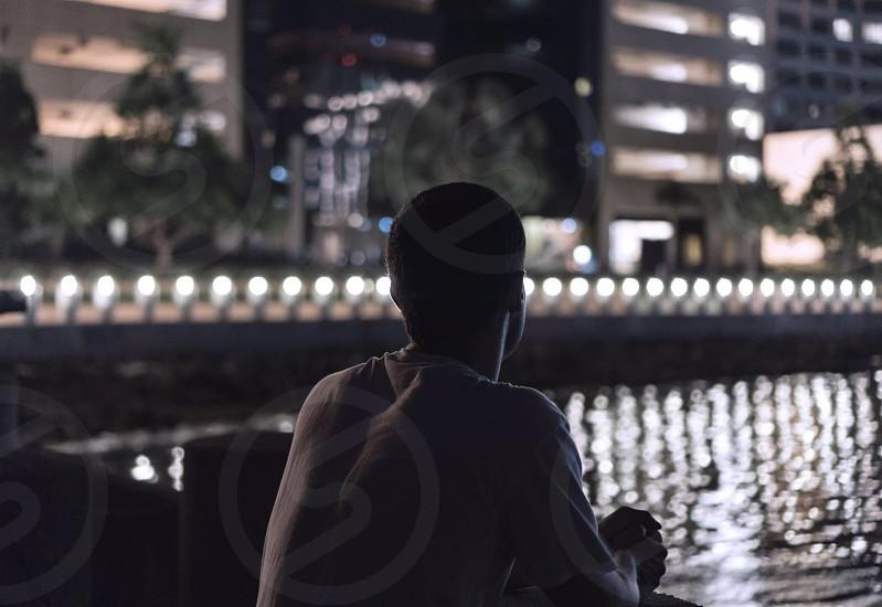 man wearing gray t-shirt standing near high-rise buildings during nighttime photo