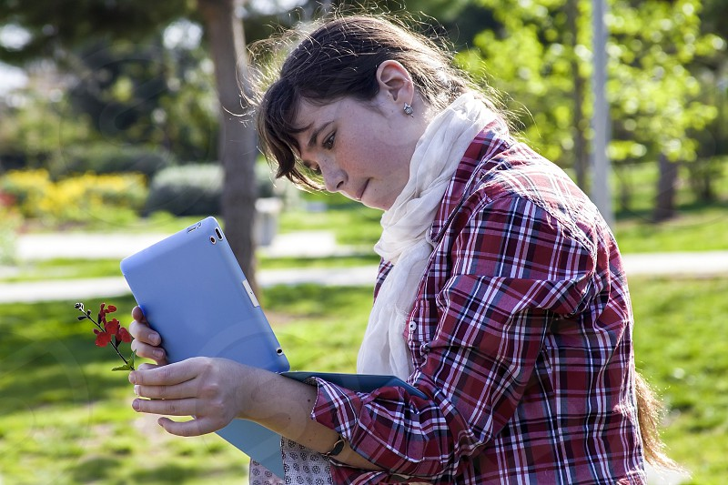 Casual teenage girl in plaid shirt and scarf using tablet and taking picture of small spring flower in sunlight photo