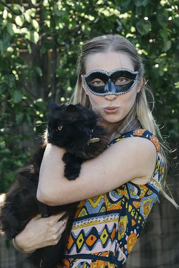 halloween hallowe'en young blonde woman girl holding black cat wearing mask pout kiss fun photo