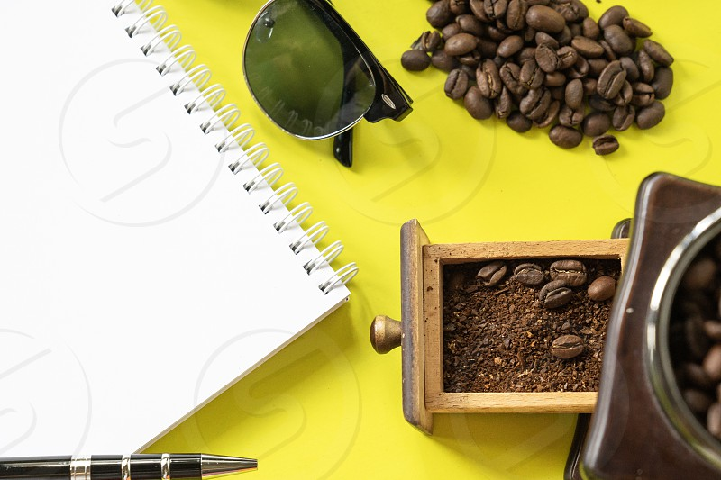 top view flat layer coofee hipster life stlye set coffee beans grinded beans in vintage wooden coffee grinder blank book  and sun glasses on yellow modern background photo