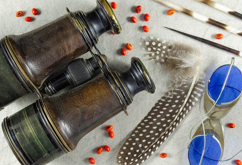 Antique French binoculars a pair of old spectacles and some coral tree seeds guineafowl feathers and porcupine quills make an interesting textured still life. photo