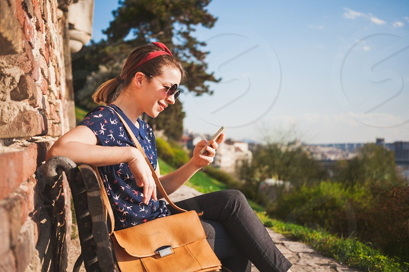 Young woman sitting in the park using smartphone photo
