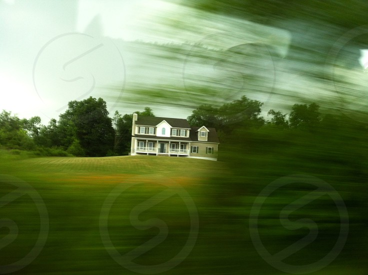 Photo taken from car of a house passing green trees and shrubs.  photo