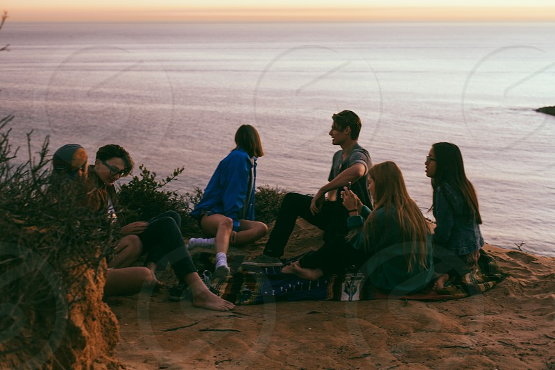 group of people sitting on the ground photo