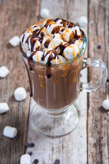 Hot chocolate topped with marshmallows and chocolate and caramel syrup photo