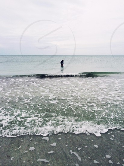 person in the ocean walking along the shore photo
