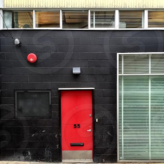 Red front door in black facade photo
