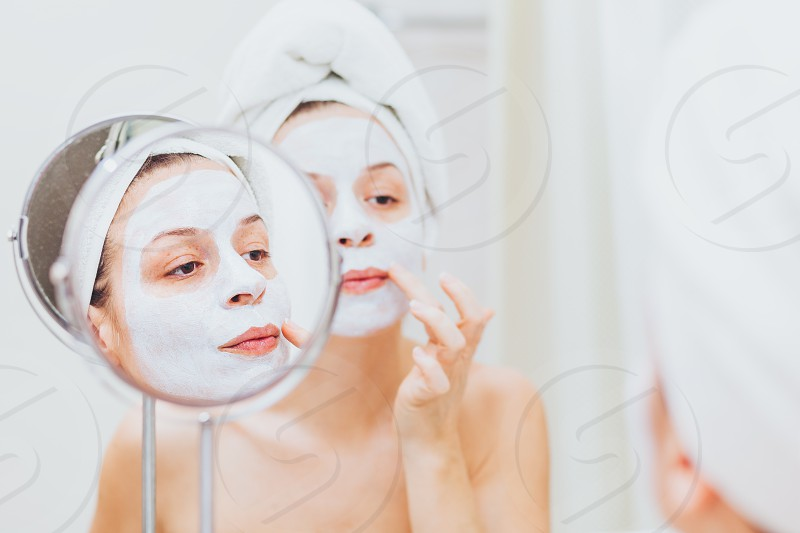 Young woman putting a mask on her face photo