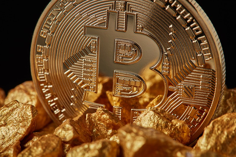 Closeup of gold nugget and Gold Bitcoin Coin on black background . Bitcoin as desirable as digital gold concept. Bitcoin cryptocurrency. photo