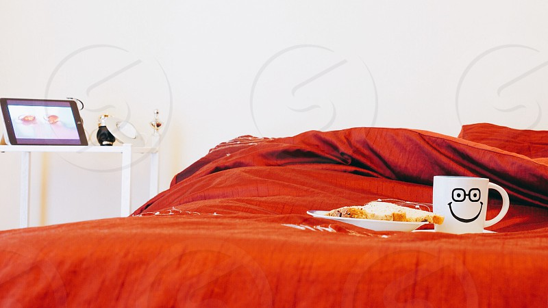 red bed sheet with white ceramic mug and breakfast in bed plate photo