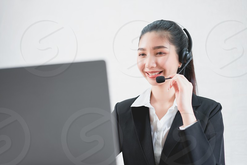 Smiling Asian woman consultant wearing microphone headset of customer support phone operator at workplace. photo