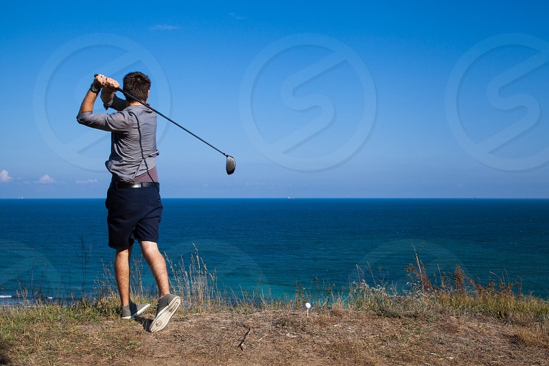 man in grey elbow sleeved shirt playing golf on cliff near body of water under blue sky during daytime photo