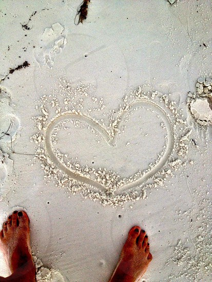 person near white sand forming heart shape during daytime photo