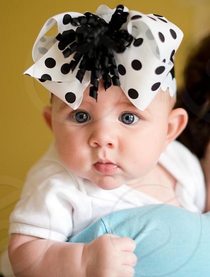 Chubby blue-eyed newborn baby with polka dot headband. photo