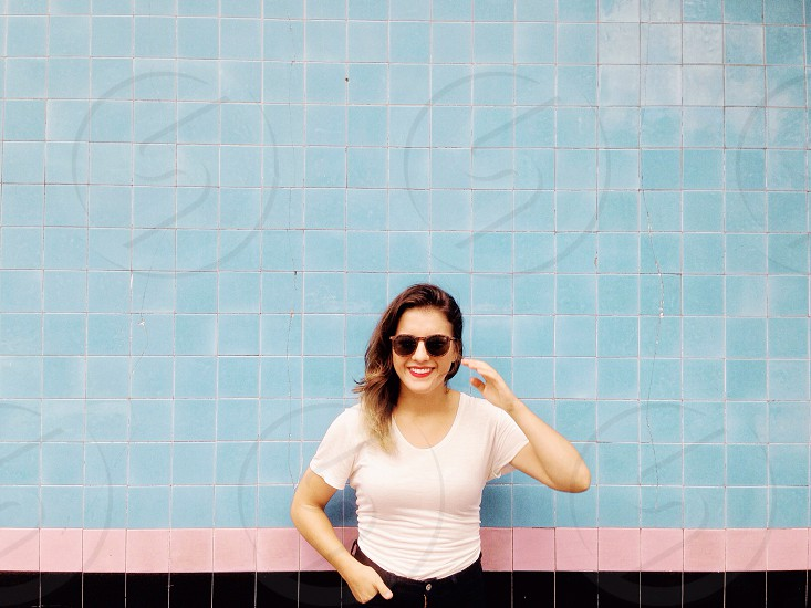 woman in white crew neck t shirt wearing black sunglasses smiling photo